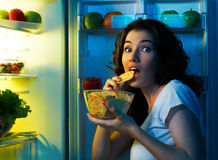 Fridge with food. A hungry girl opens the fridge Royalty Free Stock Photo