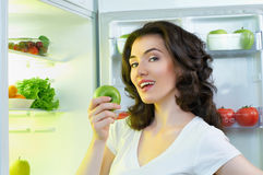 Fridge with food. A hungry girl opens the fridge Royalty Free Stock Images