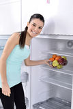 Fridge with fruit. Attractive young woman opens the fridge. beautiful girl taking fruit basket Stock Photo