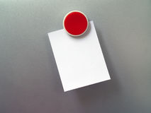 Closeup red fridge magnet with blank note on gray metal refrigerator door Stock Photo