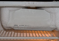 Fridge in need of defrosting. Domestic chore. Ice. Old style fridge. Ice box well frozen stock images