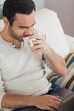 Fridsam attraktiv man som dricker kaffe, medan genom att använda hans bärbar dator Royaltyfri Foto