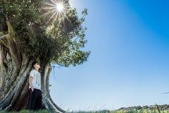 Fridsam bild av ställningar för ung man mot ett träd arkivbild