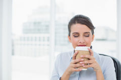 Fridsam flott brun haired affärskvinna som tycker om kaffelukten royaltyfri foto