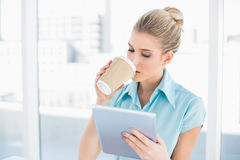 Fridsam flott kvinna som använder minnestavlan, medan dricka kaffe royaltyfria foton