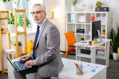 Fridsam gammal kontorsarbetare som sitter på tabellyttersidan arkivfoton