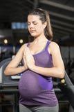 Fridsam gravid kvinna med händer tillsammans royaltyfria foton