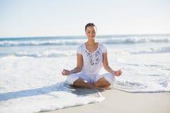Fridsam nätt kvinna i lotusblommaposition på stranden med våg r royaltyfria bilder