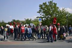 Fridsam procession av folk med r?da flaggor och ballonger p? den huvudsakliga gatan royaltyfria foton