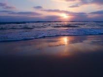 Fridsam sikt av en molnig solnedgång på den sandiga stranden med härliga reflexioner på den våta sanden royaltyfri bild