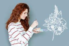 Fridsam ung målare som ler, medan arbeta på den nya målningen Royaltyfri Foto