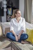 Fridsam ursnygg ung kvinna med korsat glöda för ben som tycker om lugn fotografering för bildbyråer