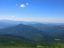 Fridsamma gröna berg som täckas av gräs under den klara blåa himlen Royaltyfri Bild