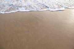 Fridsamma vågor och guld- sand, vatten, skum och sand Royaltyfria Bilder