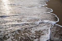 Fridsamma vågor och guld- sand, vatten, skum och sand Fotografering för Bildbyråer