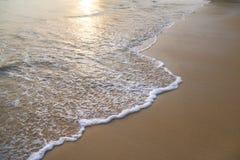 Fridsamma vågor och guld- sand, vatten, skum och sand Arkivbild