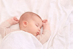 Fridsamt behandla som ett barn att ligga på en säng, medan sova i ett ljust rum arkivfoto