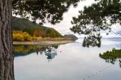 Fridsamt höstlandskap, ensligt feriefartyg på stillhetvattnet, ursprunglig bergsjö, spegelvattenreflexion, Nya Zeeland fotografering för bildbyråer