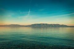 Fridsamt landskap med havet och kullar för soluppgång Royaltyfri Foto