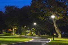 Fridsamt parkera i natten med gataljus, träd, grönt gräs och bana royaltyfri foto