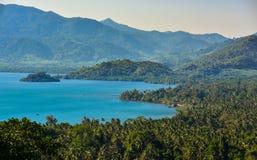 Fridsamt strand- och blåtthav med bergbakgrund Arkivbild