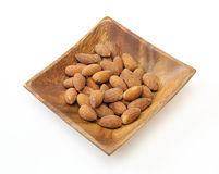 Fried almonds on a wooden plate Royalty Free Stock Photos