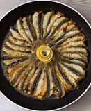 Fried anchovies on fry pan with a lemon over fishes Royalty Free Stock Images