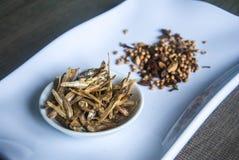 Fried Anchovies mit Mischungsgewürzen in der keramischen weißen Platte auf hölzernem Hintergrund Stockfoto