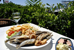 Fried anchovies on a table in the Greek tavern. Fried anchovies, seafood, vegetable and potato with the Greek sauces and white wine Stock Images