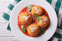 Fried arancini rice balls with tomato sauce closeup. horizontal. Fried arancini rice balls with tomato sauce close up on the table. horizontal view from above Stock Photo