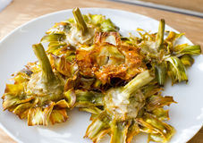 Fried artichokes. Roman fried artichokes (jewish style) with flakes of sea salt on a wooden table Royalty Free Stock Images