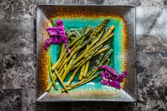 Fried asparagus on a turquoise plate. A bunch of fried asparagus on a turquoise plate with some pieces of red cabbage Stock Photos