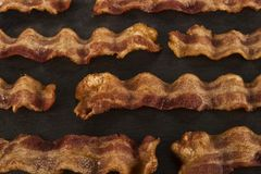 Fried bacon strips disposed on a black slate. stock photography