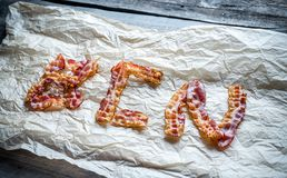 Fried bacon strips with fresh rosemary put in word Stock Photo