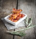 Fried bacon strips with fresh rosemary Stock Images