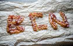 Fried bacon strips put in word Stock Photos