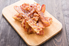 Fried bacon strips on the wooden board Royalty Free Stock Image