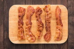 Fried bacon strips on the wooden board Stock Photography
