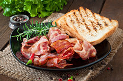 Fried bacon and toast on a black plate Stock Photo