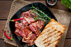 Fried bacon and toast on a black plate Royalty Free Stock Images