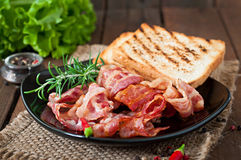 Fried bacon and toast on a black plate Royalty Free Stock Photos