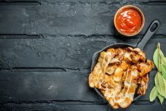Fried bacon with tomato sauce. On black rustic background stock images
