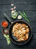 Fried bacon with tomato sauce. On black rustic background stock image