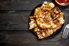 Fried bacon with tomato sauce. On a wooden background royalty free stock photos