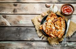 Fried bacon with tomato sauce. On a wooden background royalty free stock photo