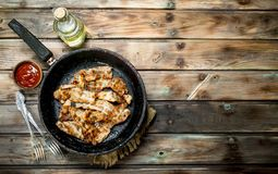 Fried bacon with tomato sauce. On a wooden background royalty free stock image