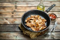 Fried bacon with tomato sauce. On a wooden background stock image