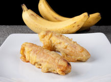 Fried Banana Pisang Goreng Indonesian Food sliced on white plate. And grey stone Royalty Free Stock Images