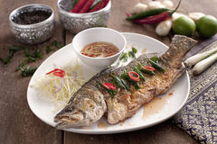Fried barramundi fish with fish sauce on white plate with lemon, Royalty Free Stock Images