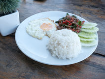 Fried basil beef with fried egg and rice. On wooden table Stock Photos